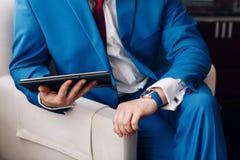Biznesmena utrzymanie cyfrowa pastylka w ręce podczas gdy siedzący na kanapie w błękitnym kostiumu na ręka drogim machinalnym zeg zdjęcia royalty free