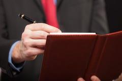 Biznesmena writing na jego agendzie Fotografia Stock