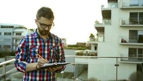 Biznesmena writing w jego osobistą organizator pozycję na balkonie zdjęcie wideo