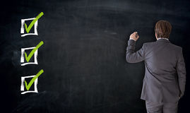 Biznesmena writing z checkbox pojęciem na blackboard obraz royalty free