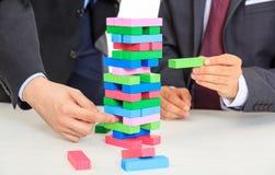 Biznesmeni bawić się drewnianych bloki gemowych Zdjęcia Stock