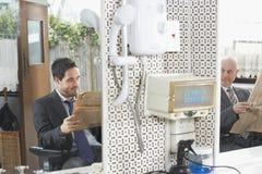 Biznesmeni Czyta gazety W Włosianym salonie zdjęcia stock