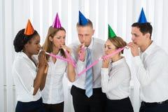 Biznesmeni Dmucha Partyjną dmuchawę W biurze Fotografia Royalty Free