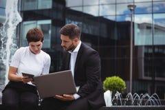 Biznesmeni dyskutuje na cyfrowej pastylce i laptopie Obrazy Stock