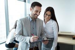 Biznesmeni dyskutuje podczas gdy używać cyfrową pastylkę w biurze zdjęcie stock