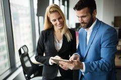 Biznesmeni dyskutuje podczas gdy używać cyfrową pastylkę w biurze obrazy stock