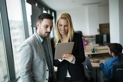 Biznesmeni dyskutuje podczas gdy używać cyfrową pastylkę w biurze fotografia stock