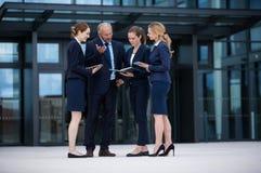 Biznesmeni dyskutuje w biurowych przesłankach Fotografia Stock