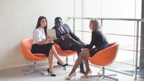 Biznesmeni i siedzą nieformalnego spotkania patrzeje dane na cyfrowej pastylce wpólnie Fotografia Royalty Free