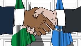 Biznesmeni lub politycy trząść ręki przeciw flaga Nigeria i Narody Zjednoczone Oficjalny spotkanie lub współpraca zbiory