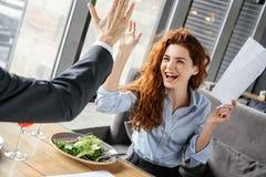 Biznesmeni ma biznesowego lunch przy restauracyjnego siedzącego łasowania wina sałatkową pije kobietą w górę dawać pięć zdjęcie royalty free