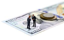 Biznesmeni miniaturyzują figurki makro- fotografię Gotówkowy pieniądze - usa moneta i banknot obraz royalty free