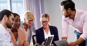 Biznesmeni oddziała wzajemnie nad cyfrową pastylką i laptopem zbiory
