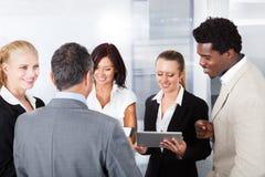 Biznesmeni patrzeje cyfrową pastylkę Fotografia Royalty Free