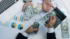 Biznesmeni próbują rozszczepiać pieniądze Żądni, niepodatni, uncooperative mężczyzna z USA dolarami, zbiory