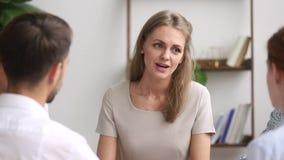 Biznesmeni siedzi wokoło stołowej ostrości na kobieta liderze oferują rozwiązanie zbiory