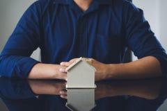 Biznesmeni stawiają wzorcowego dom na palmie I ręki zakrywali nad modelują dom dachową relacje w mediach ubezpieczenie, fotografia stock
