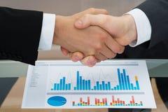Biznesmeni trząść rękę przed wykresem obrazy stock