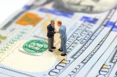 Biznesmeni trząść ręki na amerykańskim dolarze Biznesmen figurki na pieniądze tle zdjęcie stock