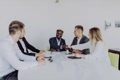 Biznesmeni trząść ręki siedzi przy konferencyjnym stołem podczas drużynowego spotkania Dwa przedsiębiorców męski handshaking robi zdjęcia royalty free