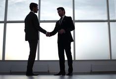 Biznesmeni trząść ręki, stoi blisko wielkiego biurowego okno fotografia royalty free
