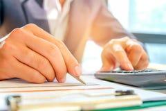 Biznesmeni używają kalkulatora i używają pióro analizować da Zdjęcie Stock