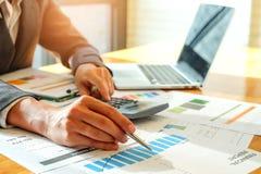 Biznesmeni używają kalkulatora i używają pióro analizować da Zdjęcia Stock