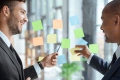 Biznesmeni wskazuje przy kleistymi notatkami podczas gdy dyskutujący pracę Obraz Stock