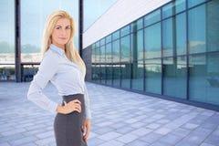 Biznesowa blond kobiety pozycja na ulicie przeciw nowożytnemu budynkowi Obrazy Stock