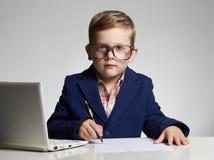Biznesowa chłopiec śmieszny dziecko pisze piórze w szkłach mały szef w biurze zdjęcia royalty free