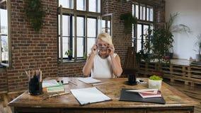 Biznesowa dama jest ubranym szkła działanie rozwija nowego nagranie i projekt siedzi przy stołem coś w zdjęcie wideo
