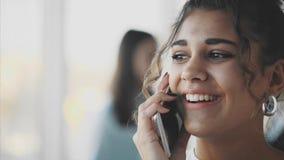 Biznesowa dama opowiada smartphone przy biurem Szczęśliwa ono uśmiecha się caucasian biznesowa kobieta ruchliwie zbiory