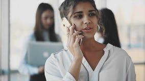 Biznesowa dama opowiada smartphone przy biurem Szczęśliwa ono uśmiecha się caucasian biznesowa kobieta ruchliwie zbiory wideo