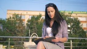 Biznesowa dama otwiera jej dzienniczek i zaczyna pisać Praca w świeżym powietrzu Dziewczyna zamienia gadżety z notatnikiem zbiory