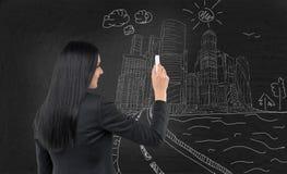 Biznesowa dama rysuje nakreślenie Moskwa Międzynarodowy Biznesowy Centre, miasto na czarnym chalkboard Zdjęcie Royalty Free