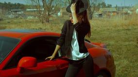 Biznesowa dama z czerwonymi wargami pozuje blisko sportowego samochodu zdjęcie wideo