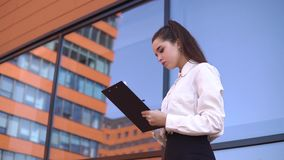 Biznesowa dziewczyna stoi blisko centrum biznesu robi notatkom w pracujących papierach 4K zbiory wideo