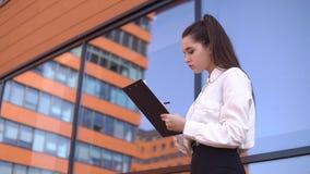 Biznesowa dziewczyna stoi blisko centrum biznesu z ciemnym włosy robi notatkom w pracujących dokumentach 4K zbiory