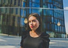Biznesowa dziewczyna w czarnym zbliżeniu na tle nowożytny budynek Obraz Royalty Free
