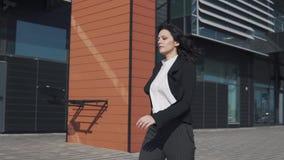 Biznesowa kobieta chodzi za nowożytnym centrum biznesu dziewczyna w garnituru spojrzeniach przy pośpiechami i zegarem zbiory