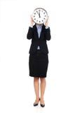 Biznesowa kobieta chuje za dużym zegarem Obrazy Royalty Free