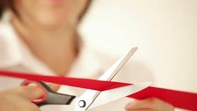 Biznesowa kobieta ciie czerwonego faborek z nożycami i otwiera wydarzenie zbiory