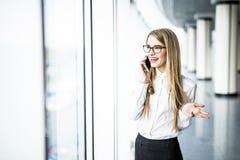 Biznesowa kobieta dyskutuje na telefonie w nowożytnym biurowym pokoju zdjęcia stock