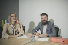 Biznesowa kobieta i mężczyzna my uśmiechamy się przy biurowym biurkiem Biznesowa dziewczyna i brodaty mężczyzna spotkania w biurz obraz stock