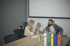 Biznesowa kobieta i mężczyzna siedzimy przy biurowym biurkiem Zmysłowa kobieta i brodaty mężczyzna biznesowego spotkania Koncentr obraz stock