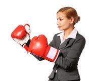 Biznesowa kobieta jest ubranym bokserskich rękawiczek uderzać pięścią odizolowywam Fotografia Stock
