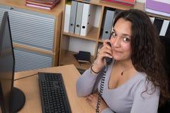 Biznesowa kobieta ma rozmowę telefoniczną siedządzą przy jej biurkiem Zdjęcie Royalty Free