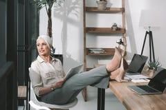 Biznesowa kobieta na worklace czytaniu z ona nogi na stole Fotografia Royalty Free