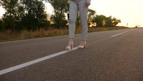 Biznesowa kobieta niesie czarną teczkę z dokumentami w ręce Kobiety iść na piechotę w białych butach i spodnia iść na asfalcie zbiory wideo