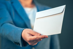 Biznesowa kobieta oferuje białą kopertę jak łapówkę Zdjęcie Royalty Free